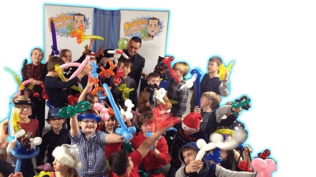 Nick Twist and the children having fun with balloons and magic.