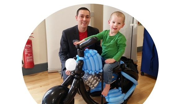 Boy on a ride-on motorbike built by Nick Twist for his borthday. Balloons available across Norfolk.
