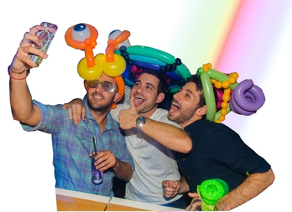 Adults having fun with their balloon hats made by Nick Twist - wedding magician in norfolk
