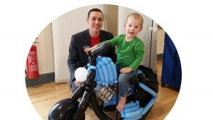 Boy on a ride-on motorbike built by Nick Twist for his birthday. Balloons available across Norfolk.